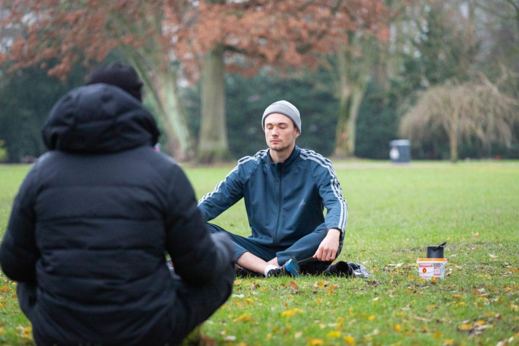 Joshua Alsen und eine Teilnehmende sind dabei zu sehen wie sie im Schneidersitz auf dem Rasen sitzen. Joshua hat seine Augen geschlossen.