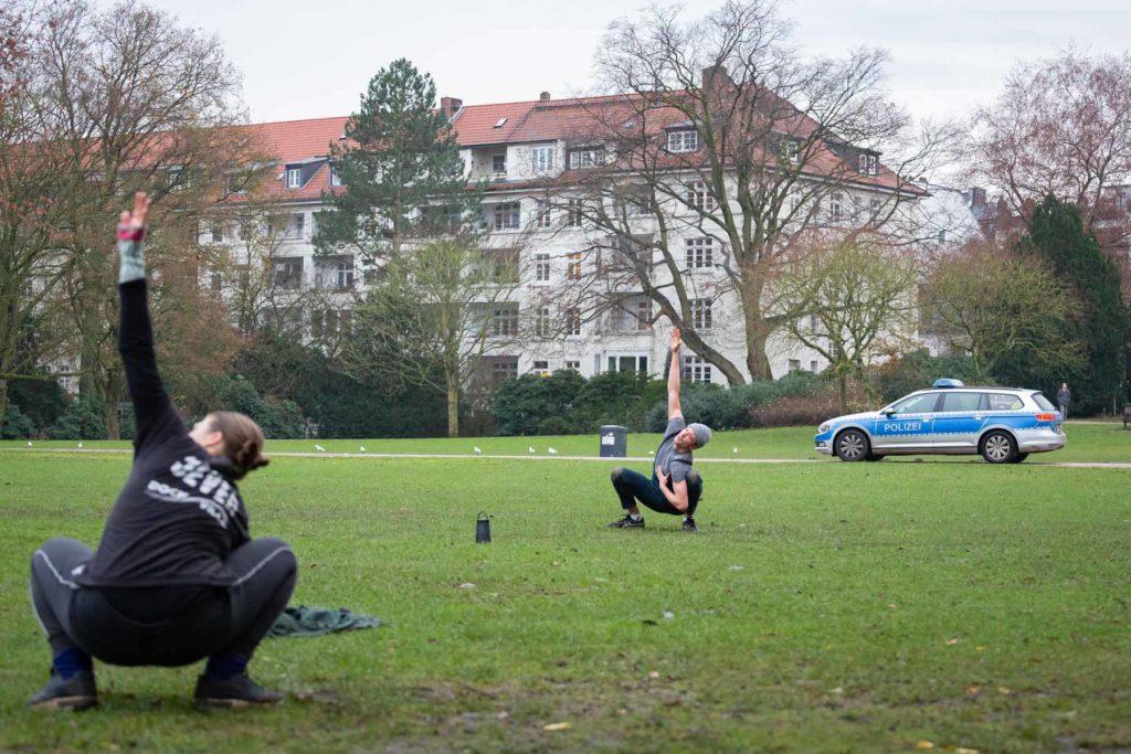 Joshua Alsen und eine Teilnehmende sind auf einer Wiese zu sehen, wie sie in der Hocke einen Arm in die Luft strecken. Im Hintergrund ist ein Streifenwagen der Polizei zu sehen.