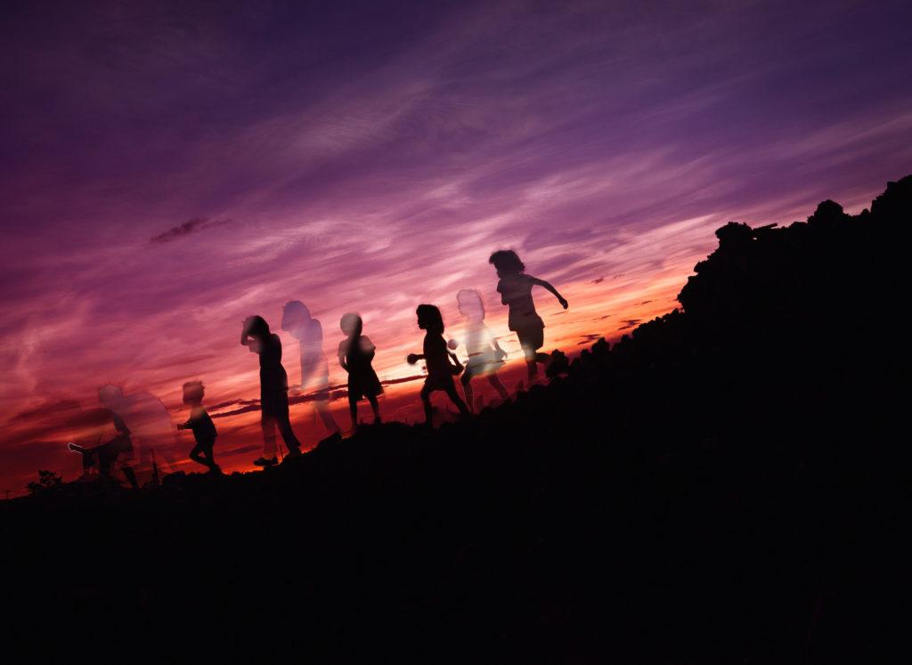 Das Foto zeigt einen lila orangen Sonnenuntergang, vor dem die Silhouetten von sechs Kindern zu sehen sind. Durch die Bearbeitung sind manche von ihnen jedoch als Schatten doppelt zu sehen. Dies dient dazu, die Frage nach dem Kinderwunsch visuell darzustellen.